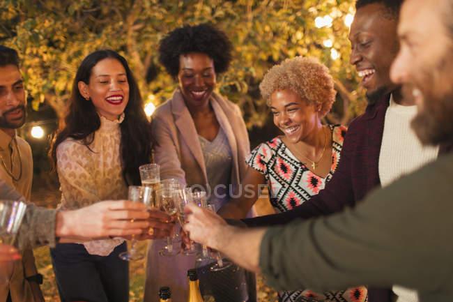 Amigos felizes que comemoram, brindando o champanhe no partido do jardim do jantar — Fotografia de Stock