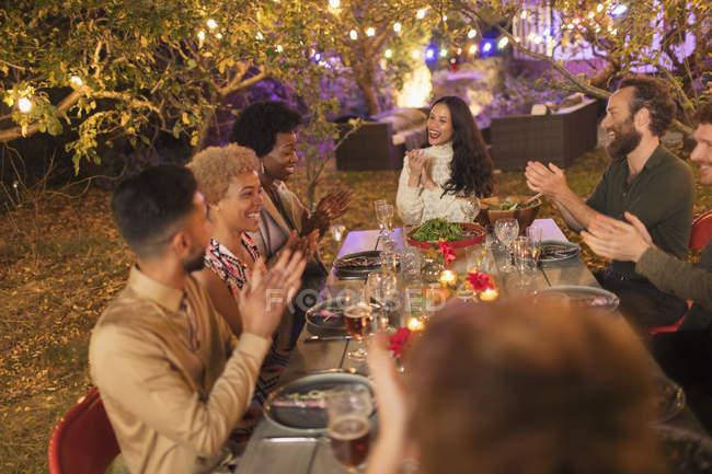 Amici applausi, godendo cena in giardino festa — Foto stock