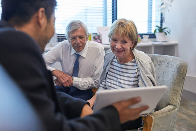 Doctor with digital tablet talking to senior couple in clinic doctors office — Stock Photo