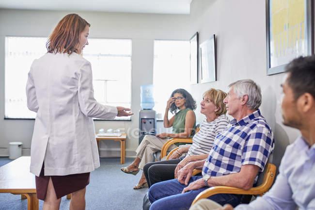 Женщина-врач разговаривает с пациентами, ожидающими в приемной клиники — стоковое фото