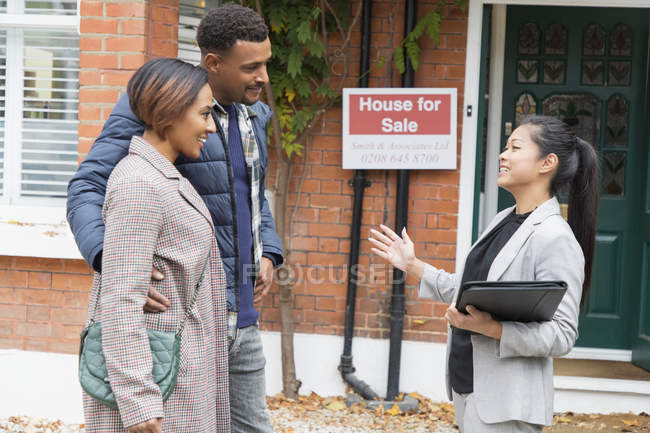 Real estate agent talking with couple outside house for sale — Stock Photo