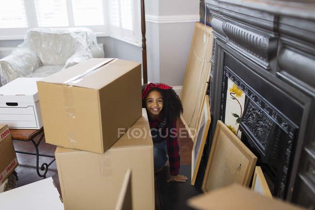Retrato lindo, chica juguetona entre cajas de cartón, casa en movimiento - foto de stock
