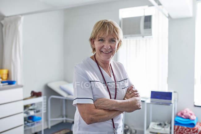 Enfermeira fêmea sênior confiável do retrato na clínica — Fotografia de Stock