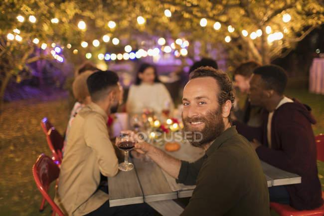 Портрет впевнений чоловік пити вино, насолоджуючись обідом сад партії — стокове фото