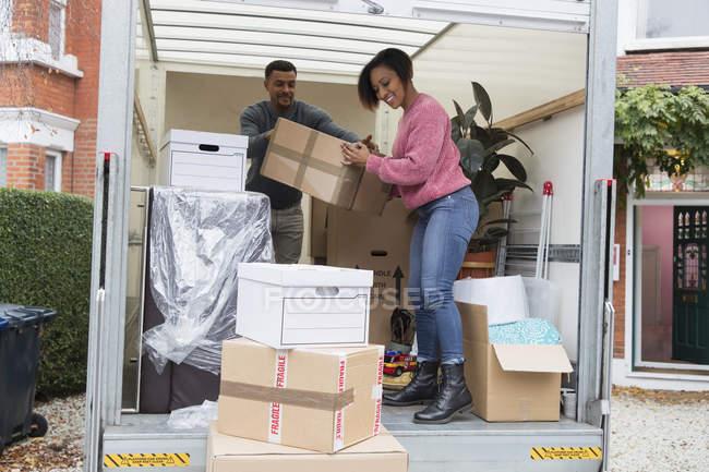 Couple unloading moving van outside new house — Stock Photo