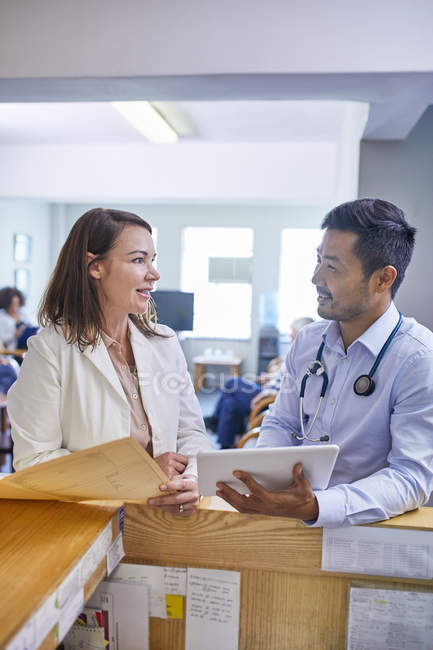 Doctors with digital tablet and medical record talking in clinic — Stock Photo