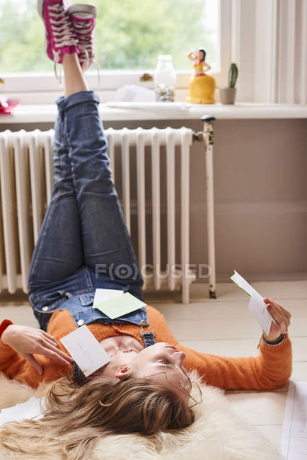 Young female college student studying with flash cards on floor — стоковое фото
