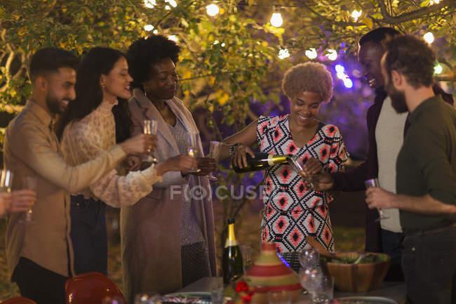 Amigos celebrando, bebiendo champán en la fiesta del jardín de la cena - foto de stock