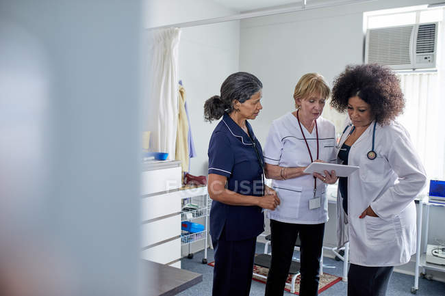 Female doctor and nurses using digital tablet in clinic examination room — Stock Photo