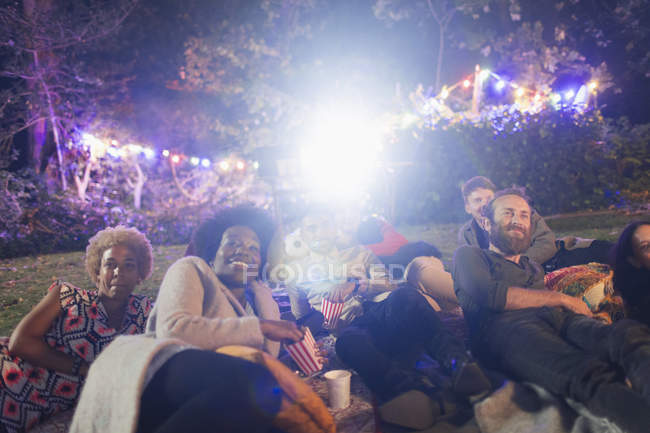 Happy friends enjoying movie in backyard — Stock Photo