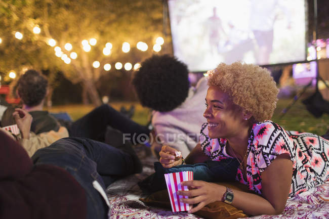 Happy woman eating popcorn, watching movie with friends in backyard — Photo de stock