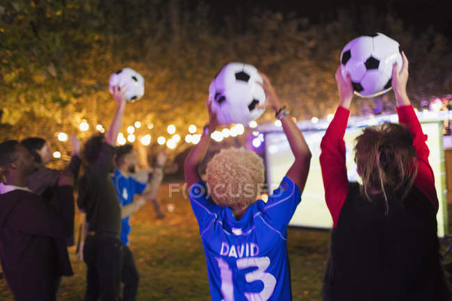 Happy friends with soccer balls cheering, watching soccer match in backyard — Stock Photo