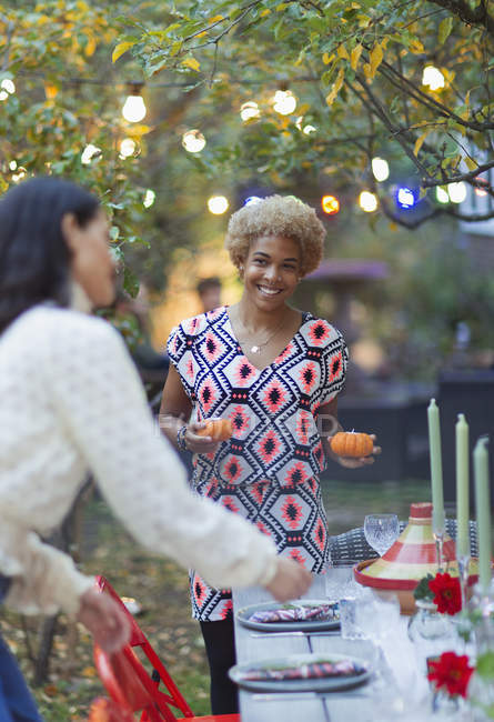 Happy women friends setting table for dinner garden party — Stock Photo