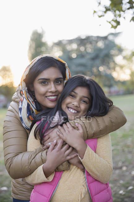 Portrait happy Muslim mother in hijab hugging daughter in park — Stock Photo