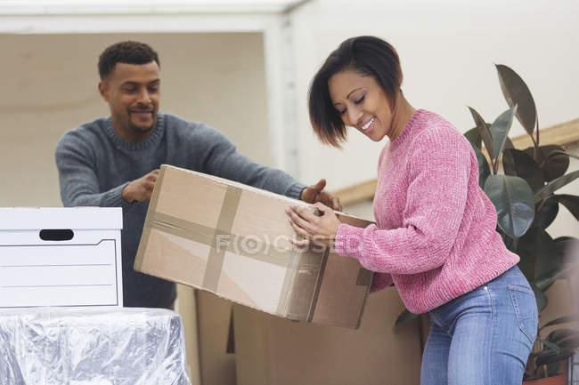 Feliz pareja moviendo casa, descargando furgoneta en movimiento - foto de stock