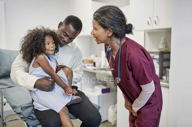 Pediatra donna che parla con padre e figlia nella sala d'esame della clinica — Foto stock