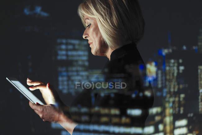 Doppia esposizione donna d'affari utilizzando tablet digitale contro le luci dei grattacieli di notte — Foto stock