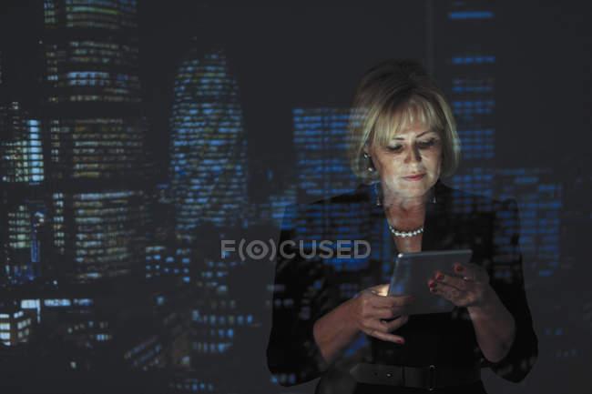 Mujer de negocios de doble exposición usando tableta digital con paisaje urbano nocturno en segundo plano - foto de stock