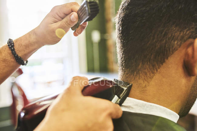 Close up male barber using trimmer on hair of customer — Stock Photo