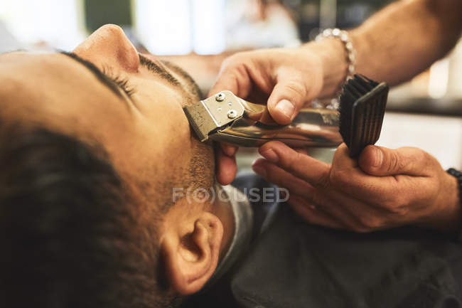 Close up uomo che riceve una rasatura in barbiere — Foto stock