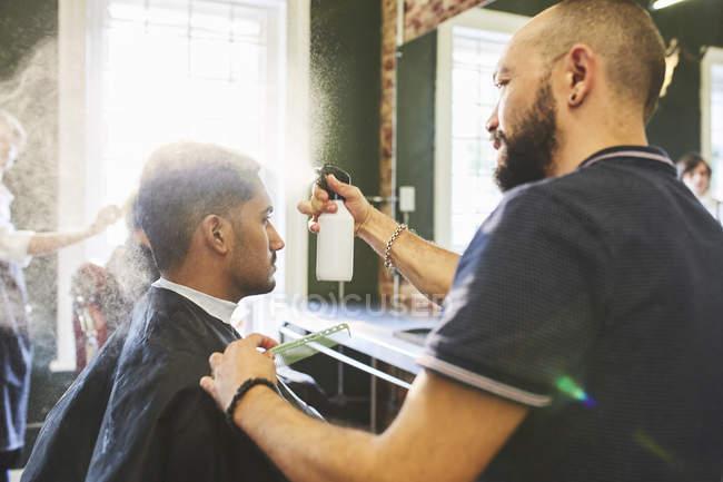 Male barber spraying hair of man in barbershop — Stock Photo