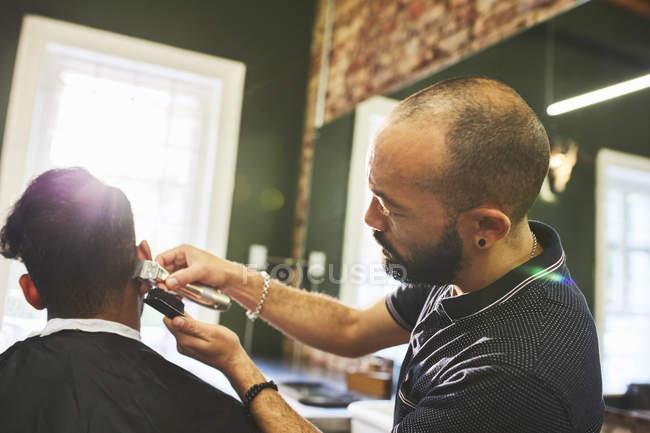 Парикмахер-мужчина с трикотажем делает клиентке стрижку в парикмахерской — стоковое фото