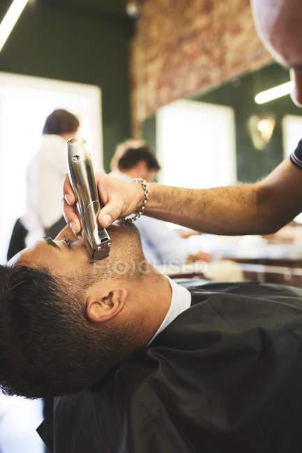Barbeiro masculino barbeando rosto de cliente na barbearia — Fotografia de Stock