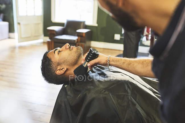 Мужчина-парикмахер побрил лицо клиентки в парикмахерской — стоковое фото