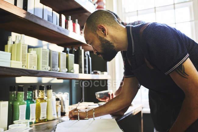 Чоловік - власник перукарні робить паперові роботи. — стокове фото