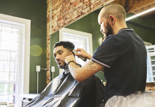 Male barber giving customer a haircut in barbershop — Stock Photo