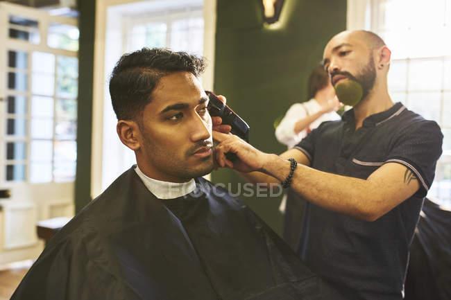 Парикмахер-мужчина брил волосы клиентки в парикмахерской — стоковое фото
