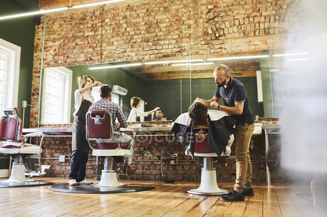 Male barbers and customers in barbershop — Stock Photo