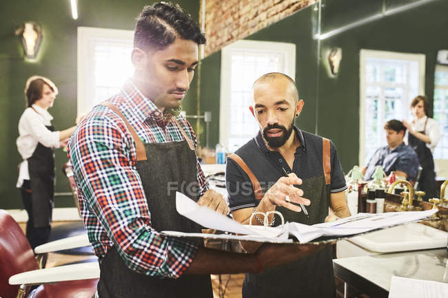 Barbeiros masculinos verificando cronograma na barbearia — Fotografia de Stock
