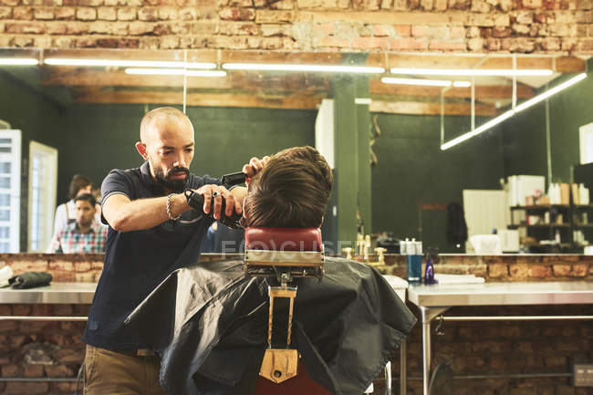 Maschio barbiere dando al cliente un taglio di capelli in barbiere — Foto stock