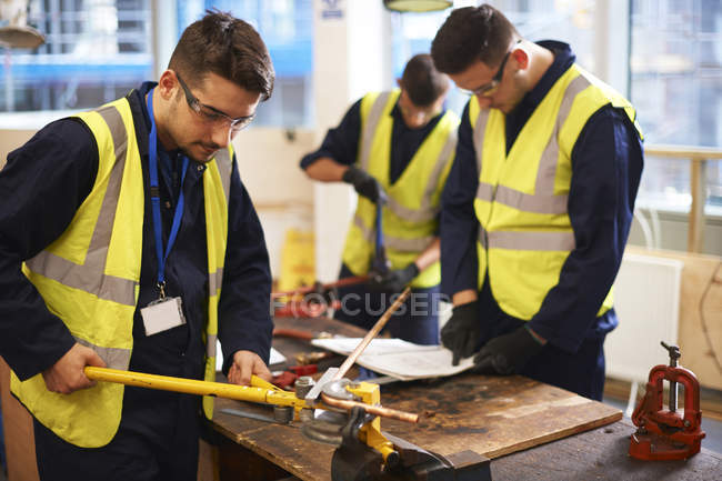 Male students using equipment in shop class workshop — Stock Photo