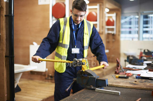 Young male student using vise grip in shop class workshop — Stock Photo