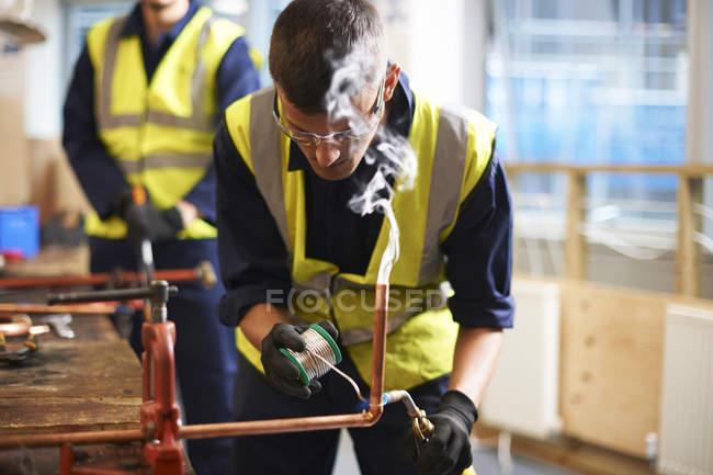 Étudiant masculin travaillant avec du cuivre dans un atelier de classe — Photo de stock