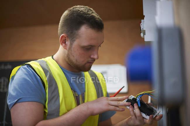 Студент-электрик осматривает выключатель в мастерской — стоковое фото