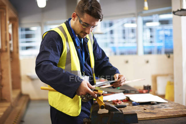 Male student using carpenters rule in shop class workshop — Stock Photo
