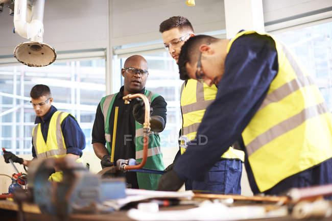 Instrutor masculino e alunos em oficina de aula de loja — Fotografia de Stock