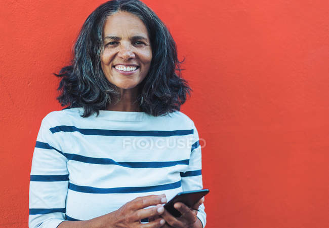 Portrait of smiling, confident woman using smartphone against red background — Stock Photo