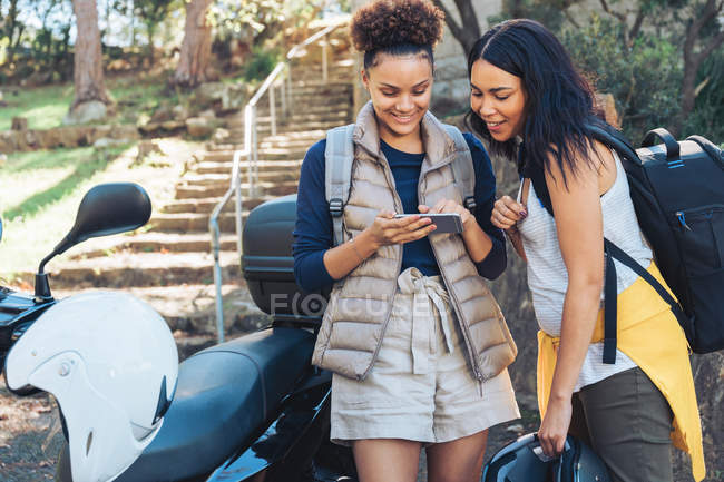 Young friends using smartphone at motor scooter — Stock Photo