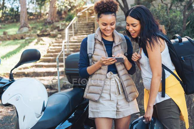 Junge Freunde nutzen Smartphone am Motorroller — Stockfoto