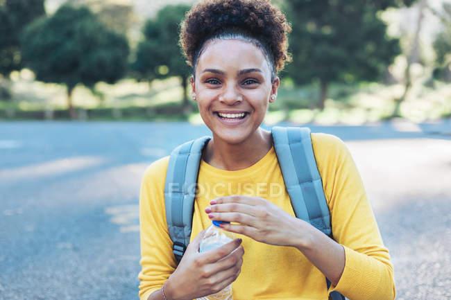 Porträt einer glücklichen, selbstbewussten jungen Frau mit Wasserflasche — Stockfoto