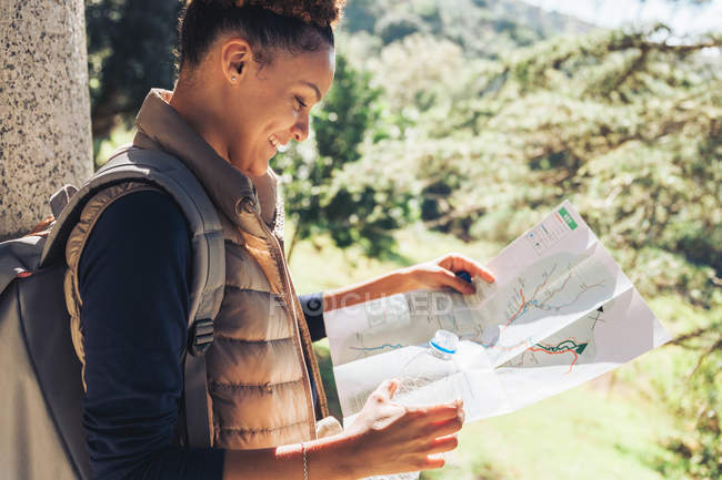 Young female hiker looking at trail map in sunny woods — Stock Photo