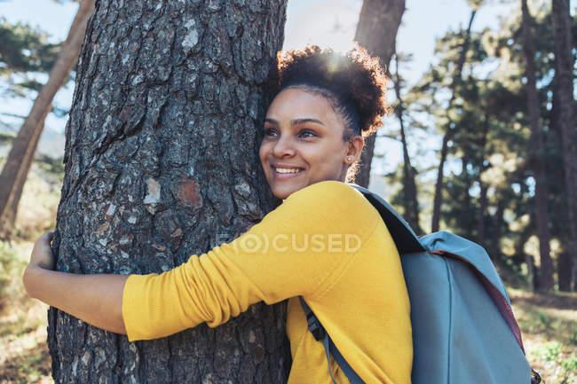 Fröhliche, unbeschwerte junge Wanderin umarmt Baum im sonnigen Wald — Stockfoto