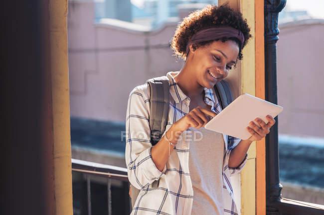 Mujer joven usando tableta digital en balcón soleado - foto de stock