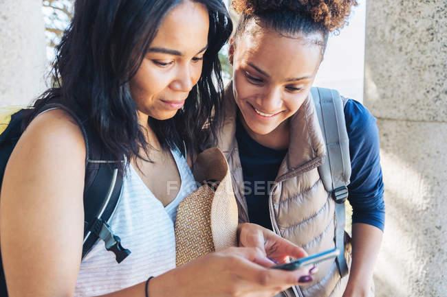 Молодые друзья с помощью смартфона — стоковое фото