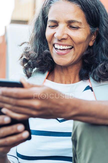Sorridente, donna felice utilizzando smartphone — Foto stock