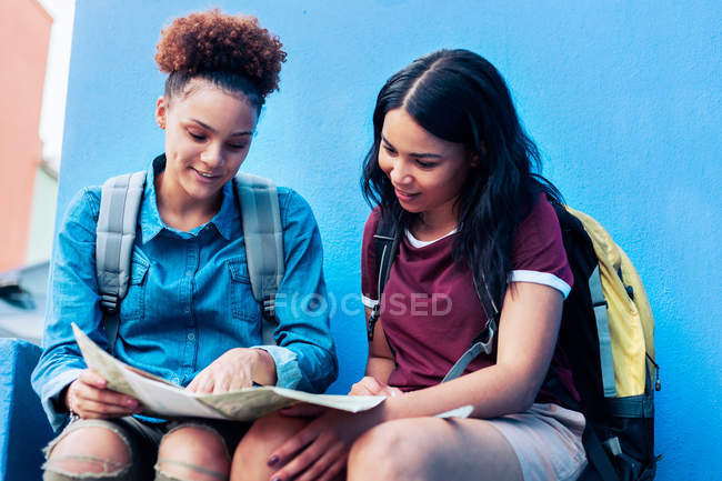 Young female backpackers looking at map — Stock Photo